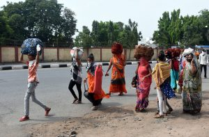 Migrant labourers walk the distance as they leave for their respective villages | See Pics