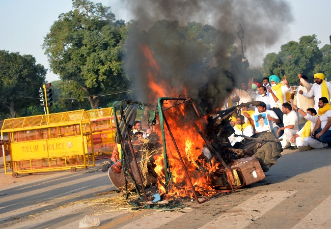 Punjab youth congress workers set ablaze a tractor during a protest
