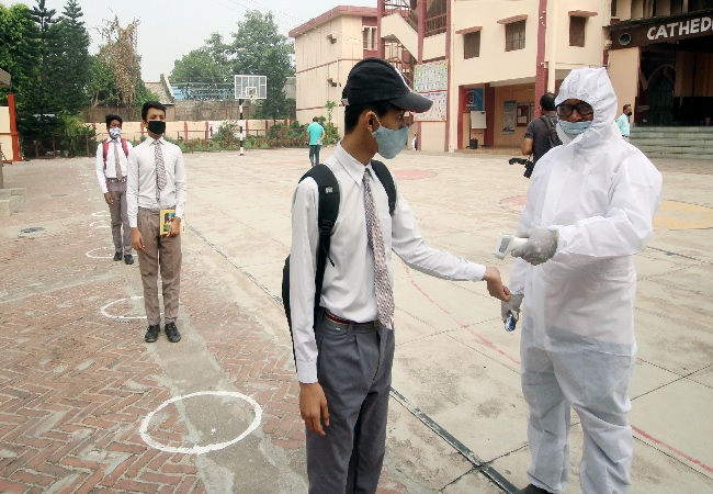 ody temperature of students is being checked as they arrive at school which reopened after COVID-19 lockdown, in Lucknow on Monday.